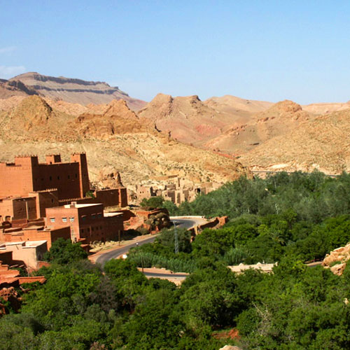 Sun drenched buildings are in the foreground of the beautiful Todgha Gorge in Morocco.