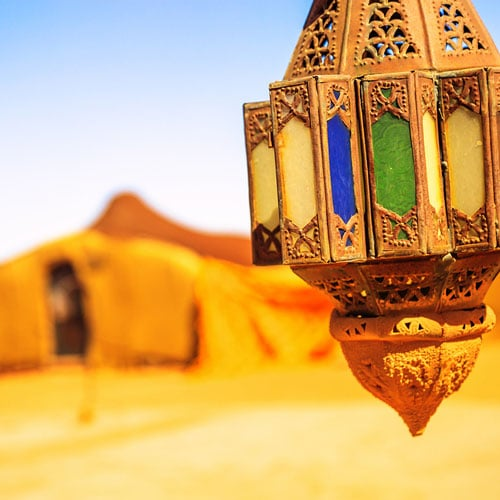 A colorful view of a nomad camp with a lamp in the forground.